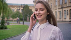 Young beautiful happy girl is talking on phone and going from university in daytime in summer, communication conception.  stock footage