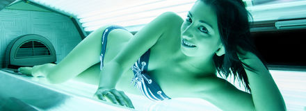 Young beautiful happy girl tanning in solarium Stock Images