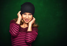 Young beautiful happy girl teenager in a black on a green backgr Stock Photos