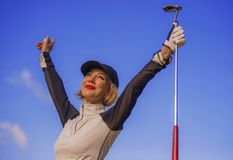 Young beautiful and happy golf player woman smiling raising arms in victory sign holding club and ball winning tournament or just stock photos