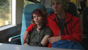 Young beautiful happy hipster couple riding by the train and looking to the window. Summer vacation. In the afternoon stock video