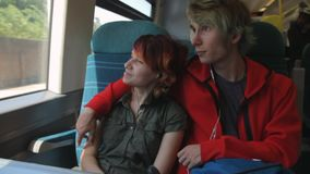 Young beautiful happy hipster couple riding by the train, looking to the window and thinking about their life in the. Future. Summer vacation. In the afternoon stock video