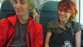 Young beautiful happy hipster couple riding by the train, talking and laughing. Summer vacation. stock video footage