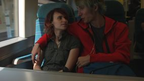Young beautiful happy hipster couple riding by the train and talking about their future. Summer vacation. stock footage