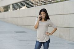 Happy latin woman on urban street city background talking on mobile phone with a sweet smile Stock Photos