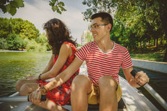 Young beautiful happy loving couple rowing a small boat on a lake. A fun date in nature. Couple in a boat. Royalty Free Stock Photos