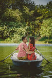 Young beautiful happy loving couple rowing a small boat on a lake. A fun date in nature. Couple hugging in a boat. Stock Photo