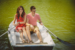 Young beautiful happy loving couple rowing a small boat on a lake. A fun date in nature. Couple hugging in a boat. Stock Photography