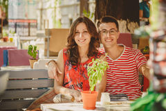 Young beautiful happy loving couple sitting at street open-air cafe, hugging. Beginning of love story. Relationship love Stock Photo