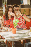 Young beautiful happy loving couple sitting at street open-air cafe, hugging, drinking yoghurt or milk. Food, lifestyle concept. Royalty Free Stock Photos