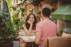 Young beautiful happy loving couple sitting at street open-air cafe looking at each other. Beginning of love story. Relationship Royalty Free Stock Image