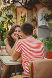 Young beautiful happy loving couple sitting at street open-air cafe looking at each other. Beginning of love story. Relationship Stock Photos