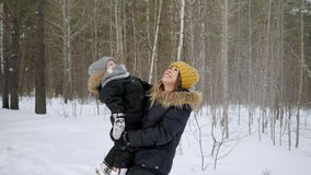 Young mom with little son in her hands is looking at snowfall in winter forest. Young beautiful happy mom with toddler son in her hands. They are looking at stock video