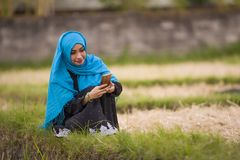 Young beautiful and happy muslim woman wearing islamic hijab head scarf and traditional clothing using internet app on mobile phon royalty free stock photos