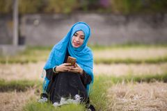 Young beautiful and happy muslim woman wearing islamic hijab head scarf and traditional clothing using internet app on mobile phon royalty free stock image