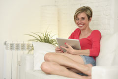Young beautiful happy 30s woman smiling using digital tablet pad at home living room couch Royalty Free Stock Photo