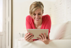 Young beautiful happy 30s woman smiling using digital tablet pad at home living room couch Stock Photography