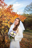 Young beautiful happy slim smiling bride on autumn forest backgr Royalty Free Stock Image
