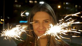 Young beautiful happy smiling girl holding sparkler on the street. Holiday concept. Girl with sparklers in the street Stock Photography