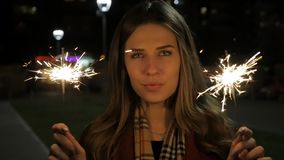 Young beautiful happy smiling girl holding sparklers, posing in street. Woman with sparklers in the street. Holiday. Concept stock footage
