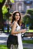 Young beautiful happy smiling lady walking on the street, holding paper cup of coffee. Model wearing stylish clothes and Royalty Free Stock Photography