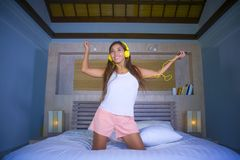 Young beautiful and happy student woman Asian Latin ethnicity mixed listening to music with headphones in bed singing and dancing stock photos