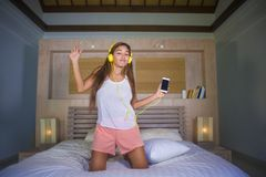 Young beautiful and happy student woman Asian Latin ethnicity mixed listening to music with headphones in bed singing and dancing Stock Photography