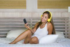 Young beautiful and happy student woman Asian Latin ethnicity mixed listening to music with headphones in bed singing and dancing Stock Image