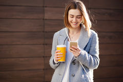 Young beautiful happy stylish hipster girl with cocktail, smoozy drink and smartphone Royalty Free Stock Photo