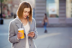 Young beautiful happy stylish hipster girl with cocktail, smoozy drink and smartphone Stock Image