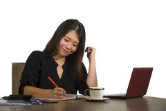 Young beautiful and happy successful Asian Korean businesswoman working relaxed at office computer desk smiling confident posing c stock photos