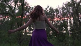 Young beautiful happy woman with big breast circling barefoot in the woods in a purple skirt at twilight time stock video
