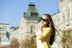 Young beautiful happy woman calling by phone in Moscow Stock Image