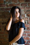 Young beautiful happy woman in casual clothes against brick wall royalty free stock photography