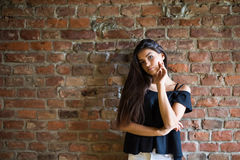 Young beautiful happy woman in casual clothes against brick wall stock images