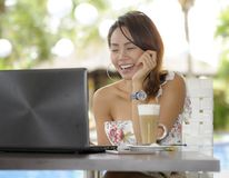 Beautiful happy woman in Summer dress outdoors at nice coffee shop having breakfast networking or working with laptop computer Royalty Free Stock Image