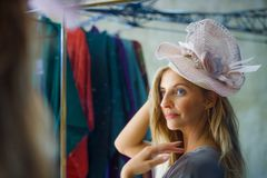 Young beautiful and happy woman enjoying shopping trying out clothes and vintage hat looking at mirror in beauty fashion store smi stock images