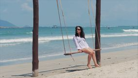 Young Beautiful Happy woman enjoying on a swing on the beach against the ocean background. stock video footage
