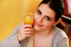 Young beautiful happy woman holding glass of orange juice Stock Photography