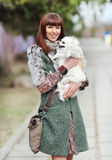 Young beautiful happy woman holding her small dog Royalty Free Stock Photography