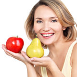 Young beautiful happy woman holds the apple and pear. Stock Photo