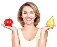 Young beautiful happy woman holds the apple and pear. Royalty Free Stock Image