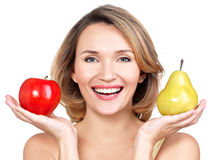 Young beautiful happy woman holds the apple and pear. Royalty Free Stock Images