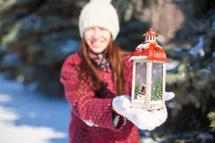 Young beautiful happy woman with red Christmas lantern in the snow Royalty Free Stock Image