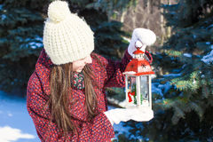 Young beautiful happy woman with red Christmas lantern in the snow Stock Photo