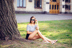 Young beautiful happy woman in round sunglasses sitting on the g. Rass in the park royalty free stock image