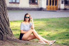 Young beautiful happy woman in round sunglasses sitting on the g. Rass in the park royalty free stock images