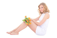 Young beautiful happy woman sitting with orange tulips isolated Royalty Free Stock Photos