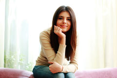 Young beautiful happy woman sitting on the sofa Royalty Free Stock Photos
