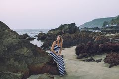Young beautiful happy woman sitting on stones on sea shore in lo Royalty Free Stock Photos